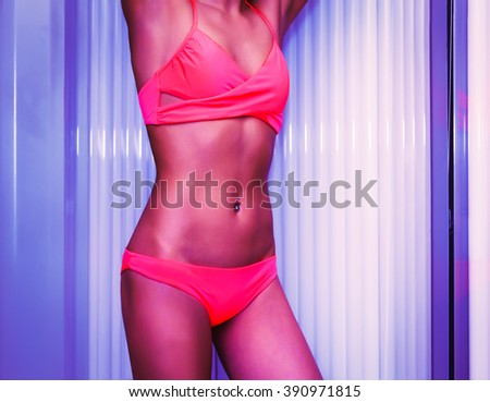Slim young woman standing in solarium getting sun tan - stock photo