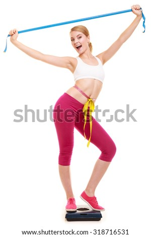 Slimming and weight loss. Happy joyful young woman girl measuring with tape measures on weighing scale. Successful girl with raised arms hands. Healthy lifestyle concept. Isolated on white. - stock photo