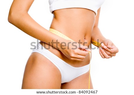 Slimming woman body in panties with measure on white background - stock photo