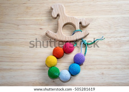 Sling beads with horse toy on a wooden table with copy space