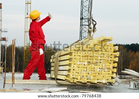 slinger builder in uniform and helmet operating with straps at construction area - stock photo