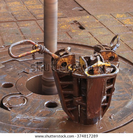 Slip on the rotary table while drilling oil well and pipe being rotated - stock photo
