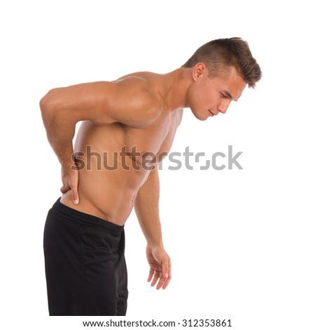 Slipped Disc. Half naked muscular man holding lower back in pain. Three quarter length studio shot isolated on white. - stock photo
