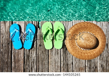 Slippers and hat at jetty by the sea - stock photo