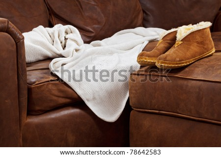 Slippers and throw blanket on a soft leather sofa - stock photo