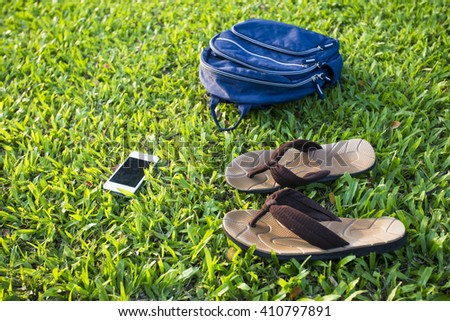 Slippers, bags and smartphones green grass,holiday