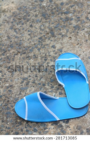 Slippers blue on a background of cement. - stock photo