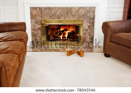 Slippers by the fire in a cozy living room - stock photo