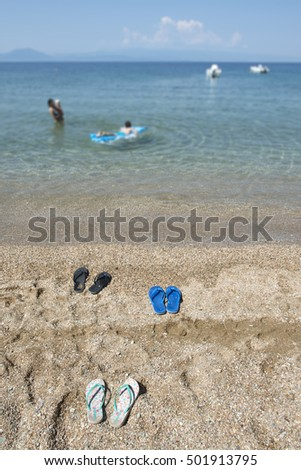 Slippers in the sand on the beach and people at sea.