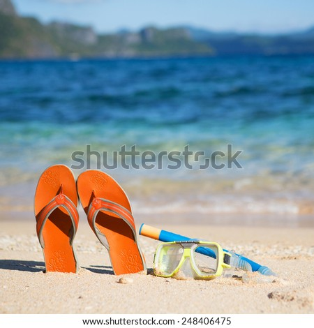 Slippers, mask and snorkel on sand beach near the water
