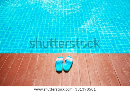 Slippers near the swimming pool - stock photo