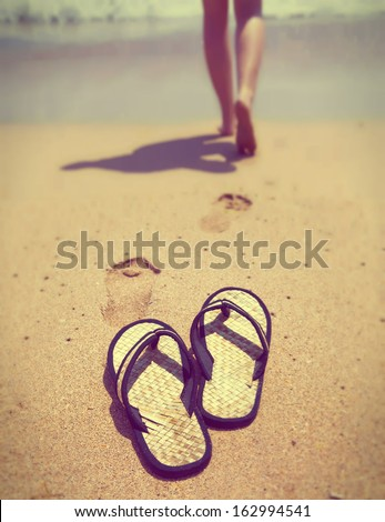 slippers on sand, and female feet out of focus ,with a retro effect - stock photo