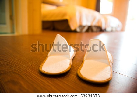 Slippers on the floor of hotel room. - stock photo