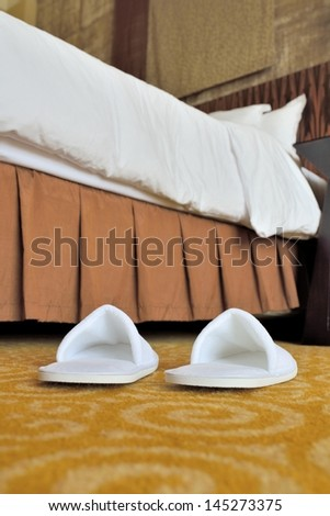 Slippers on the floor of hotel room by the bed