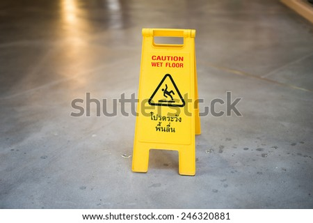Slippery caution sign with bilingual languages. - stock photo