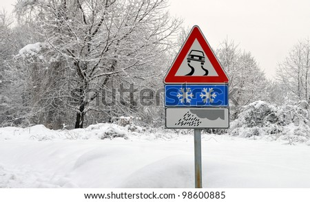 Slippery road sign in snow. Severe weather conditions - stock photo