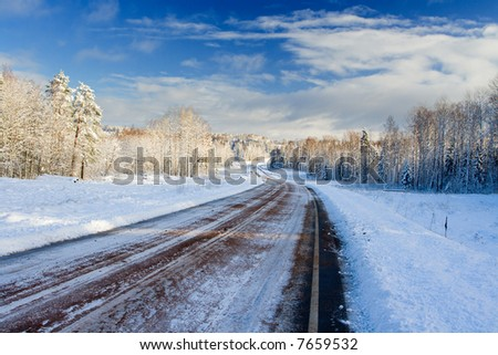 Slippery twisting road taking place on a snow wood - stock photo