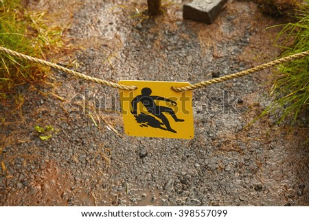 Slippery warning sign on mountain trail - stock photo
