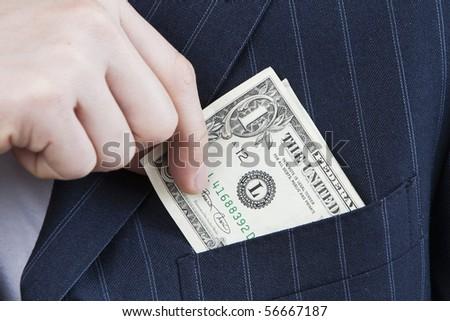 Slipping Money into Pocket closeup of businessman slips money into suit front pocket - stock photo