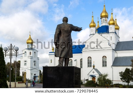 Slonim, Belarus - October, 5, 2017: The statue of Lenin points to the church.The Transfiguration Cathedral is a temple located in the city of Slonim.