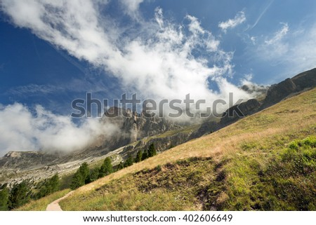 sloping meadow with Dolomites in the background - stock photo