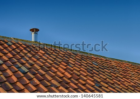 Sloping tiled roof against blue sky with single metal flue - stock photo