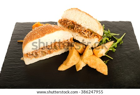 Sloppy Joe Minced Meat Sandwich with French Fries and Green Salad. Tasty Healthy Burger Bread with Potato and Minced Meat Over White Background, Isolated on a Black Shredding Plate Board - stock photo
