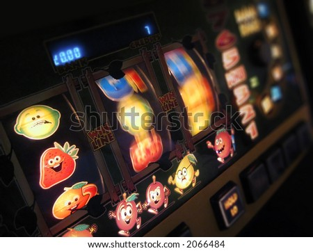 slot machine wheels spinning, reels brightly lit, differential focus - stock photo