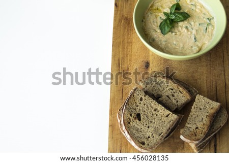 "Slovak spread made from sheep cheese called ""bryndza"", butter, yoghurt and herbs with baked breads. Flat lay food on white wooden table. - stock photo"