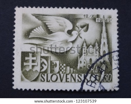 SLOVAKIA - CIRCA 1942: A stamp printed in Slovakia shows a dove and St Stephen's Cathedral, circa 1942. - stock photo