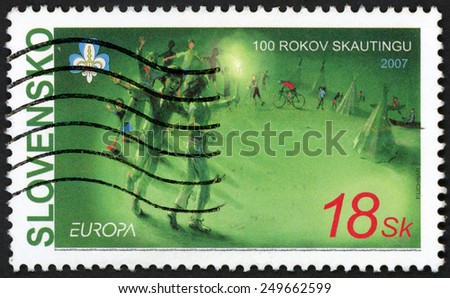 SLOVAKIA - CIRCA 2007: post stamp printed in Slovensko shows playing kids & tents; 100 years of scouting; Europa; Scott 520 A314 18sk green, circa 2007 - stock photo