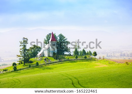 Slovakia rural small church in the hills and trees panorama - stock photo