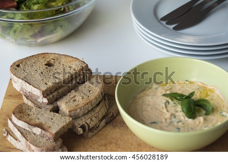 "Slovakian spread made from sheep cheese called ""bryndza"", butter, yoghurt and herbs with baked breads and fresh summer salad. Closeup on served food on white wooden table. - stock photo"