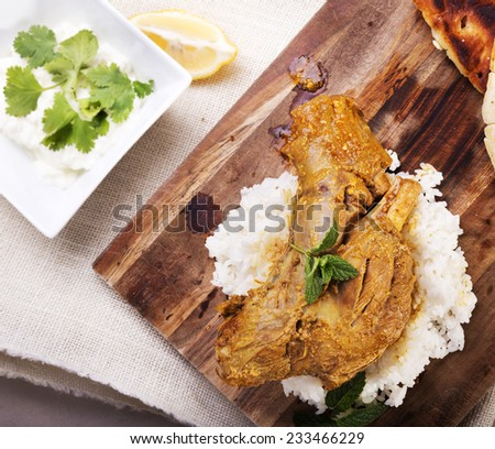 Slow cooked lamb shanks served on wooden board with rice and gluten free naan bread - stock photo