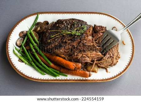 Slow cooked pot roast with carrots, green beans, onions, garlic and gravy on a white porcelain platter with gold rim and serving fork against a gray tablecloth.  - stock photo
