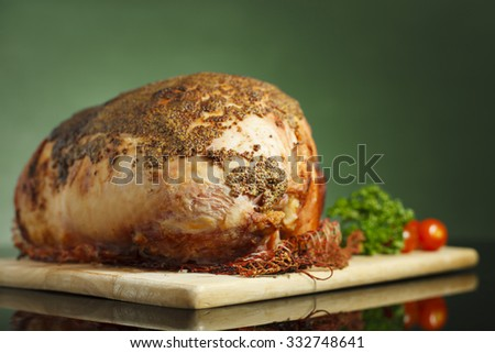 Slow cooked roast beef  covered with mustard sauce and baby tomatoes on reflective surface and green background - stock photo