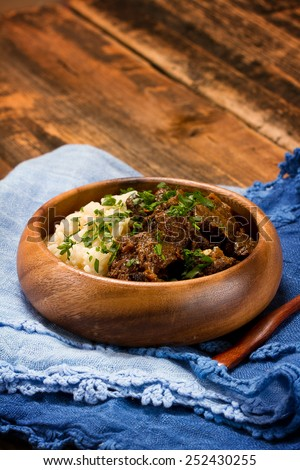 Slow cooked spicy beef curry with rice in a wooden bowl - stock photo