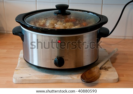Slow cooker with wooden spoon on chopping board cheep winter cooking - stock photo