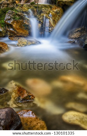 slow exposure waterfall with rocks and moss and reflections/ Out of the Rocks