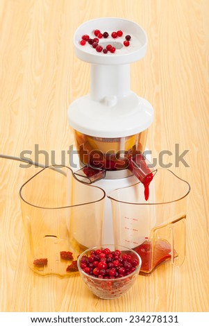 slow juicer makes cranberry juice - stock photo