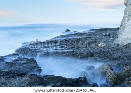 Slow motion captures the artistic look and feel of the ocean water as it hugs a reef during daybreak.  - stock photo