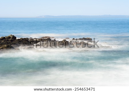 Slow motion scenic of a beautiful reef with seawater rushing over a rugged offshore reef in Laguna Beach, California. - stock photo