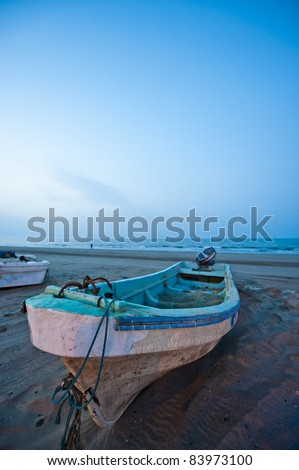 Slow shutter evening shot of a fishing boat on a beach in the Seeb area in Oman. - stock photo