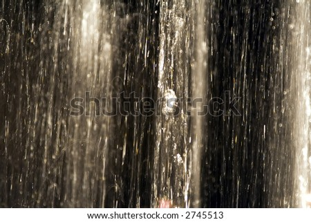 Slow shutter photograph from inside a lit fountain at night. - stock photo