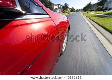 Slow shutter speed mounted camera shot taken from a car driving at speed through a suburban neighborhood. - stock photo