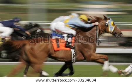 Slow shutter speed rendering of racing horses and jockeys - stock photo