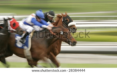 Slow shutter speed rendering of racing jockeys and thoroughbred horses