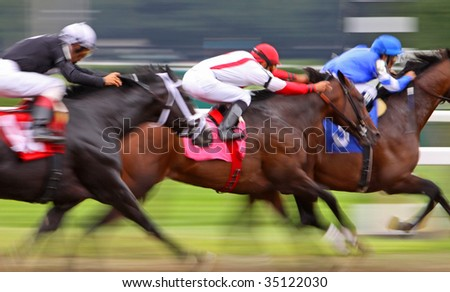 Slow shutter speed rendering of three jockeys racing their horses for the win in a thoroughbred horse race. - stock photo