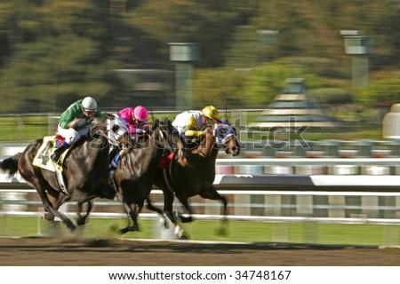 Slow shutter speed rendering of three racing jockeys and horses - stock photo