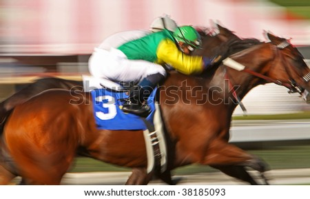 Slow shutter speed rendering of two jockeys struggling for the win in a thoroughbred horse race - stock photo